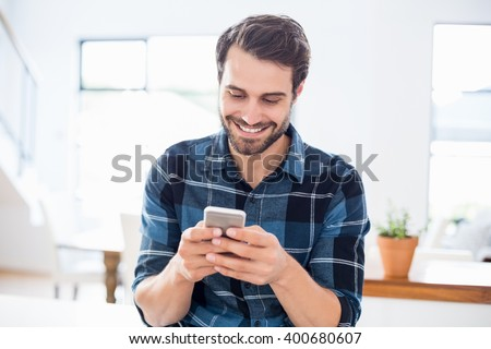 Happy man using mobile phone at home - stock photo