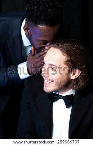 Happy man whispering into man's ear, gossiping. - stock photo