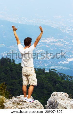 Happy man with arms raised up - stock photo