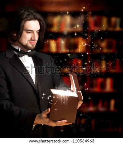 Happy Man with Bowtie Opening a Gift Box - stock photo