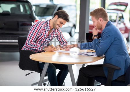 Happy man with car dealer buying a car signs the contract in car showroom - stock photo