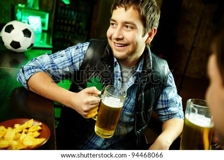 Happy man with glass of beer looking aside in pub - stock photo