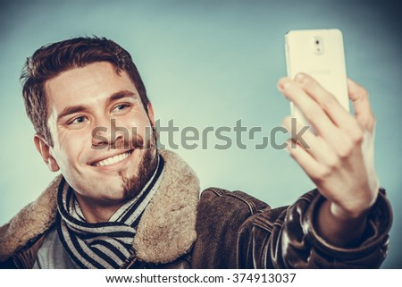 Happy man with half shaved face beard hair taking selfie self photo with smartphone camera. Smiling handsome guy on blue. Skin care and hygiene. Instagram filter. - stock photo