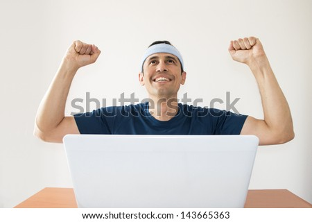 Happy man with hands raised in the air after winning a sports bet - stock photo