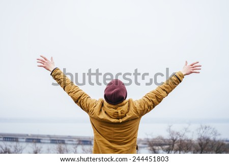 Happy man with hands up looks into the horizon - stock photo