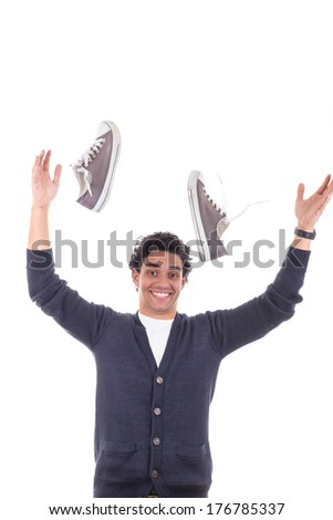 happy man with sneakers throwing them away and smiling - stock photo