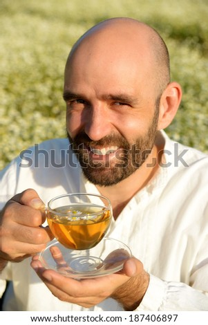 happy man with tea in a chamomile field - stock photo