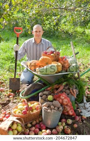 Happy man with vegetables harvest in garden - stock photo