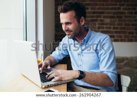 Happy man working on laptop at restaurant - stock photo