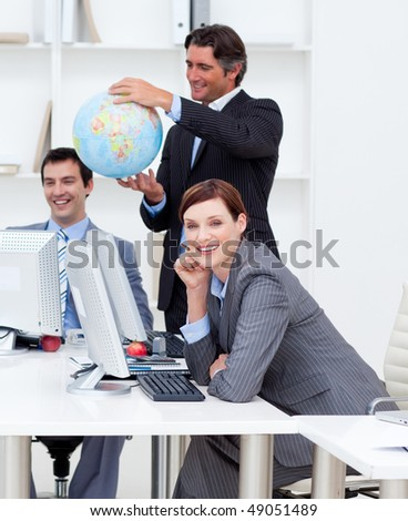 Happy manager holding a terrestrial globe with his team working at computers. Business concept. - stock photo