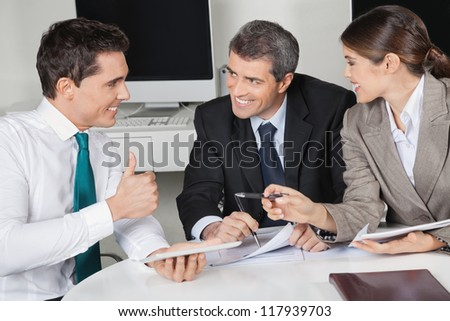 Happy manager in business meeting holding his thumb up - stock photo