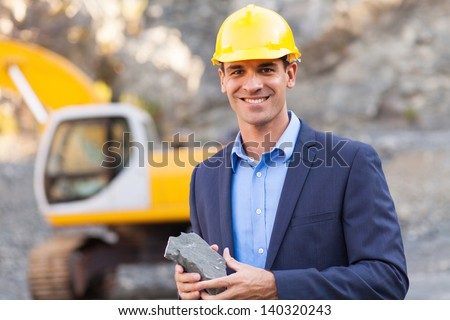 happy manager in mining site holding ore - stock photo