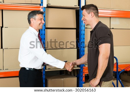 Happy Manager Shaking Hands With Worker In Warehouse - stock photo