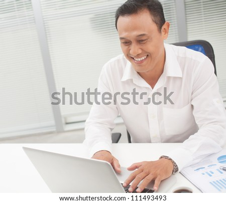 Happy manager typing on laptop at his table - stock photo
