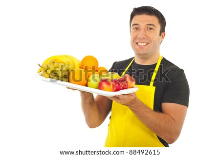 Happy market worker with yellow apron holding fruits isolated on white background - stock photo