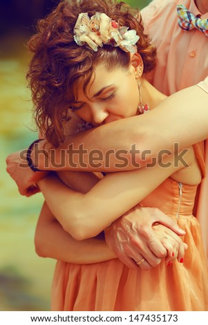 Happy marriage concept. Portrait of a beautiful couple of hipsters in trendy clothing hugging. Bride kissing groom's hand. Peach colored clothing. Wedding day. Close up. Outdoor shot - stock photo