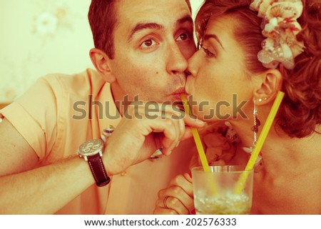 Happy marriage concept. Portrait of a beautiful married couple of hipsters in trendy clothing drinking mojito and kissing in vintage restaurant. Wedding day. Retro style. Close up. Indoor shot - stock photo