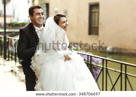 Happy married couple bride and groom running & laughing in old french street - stock photo
