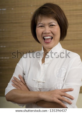 Happy mature Asian woman laughing - stock photo