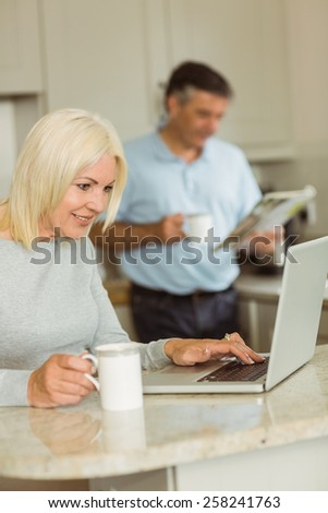 Happy mature blonde using laptop at home in the kitchen - stock photo
