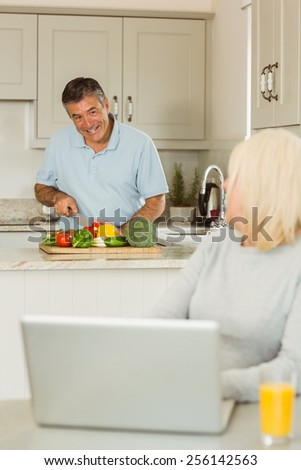 Happy mature blonde using laptop talking with husband at home in the kitchen - stock photo