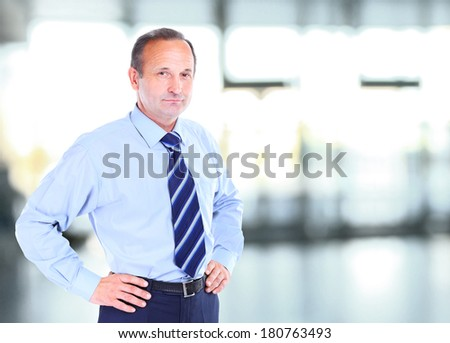 Happy mature business man looking at camera with satisfaction at office - stock photo