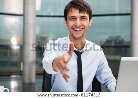 Happy mature business man offering a welcoming hand sitting at his desk. Horizontal shot - stock photo
