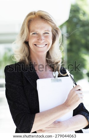 Happy mature business woman smiling  - stock photo