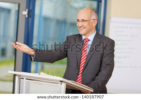 Happy mature businessman gesturing while standing at podium in office - stock photo