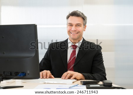 Happy Mature Businessman Using Computer In Office - stock photo
