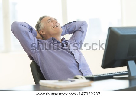 Happy mature businessman with hands behind head looking up while sitting at desk in office - stock photo