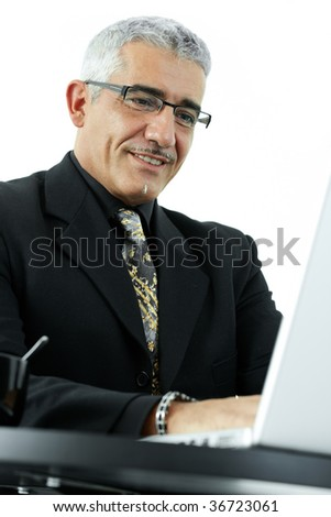 Happy mature businessman working on laptop computer, smiling, isolated on white background. - stock photo