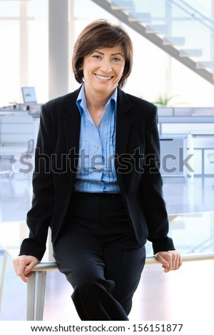 Happy mature businesswoman in office sitting on desk, smiling. - stock photo