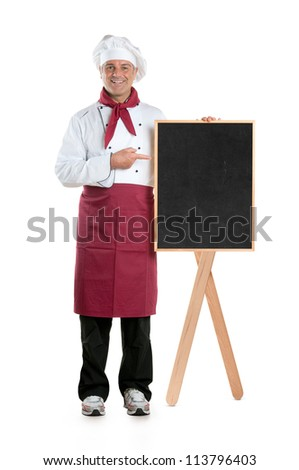 Happy mature chef showing dish of the day on a black board isolated on white background - stock photo