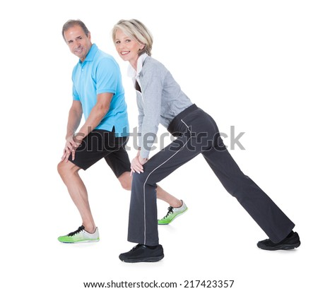 Happy Mature Couple At Gym In Fitness Attire Exercising On White Background - stock photo