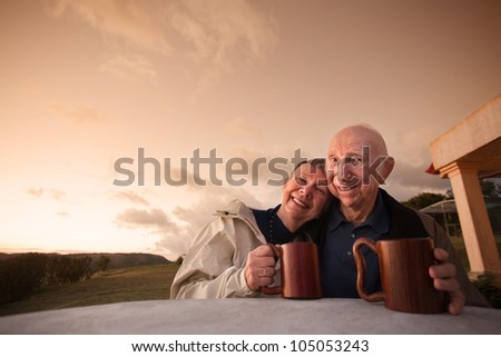Happy mature couple at table outside with coffee mugs - stock photo