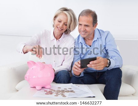 Happy Mature Couple Calculating Coin In The Piggybank - stock photo