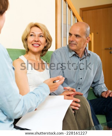 Happy mature couple discussing details of private insurance with agent  - stock photo