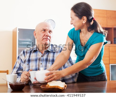 Happy mature couple having tea at home interior  - stock photo