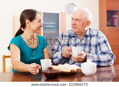 Happy mature couple having tea with jam at home. Focus on man - stock photo