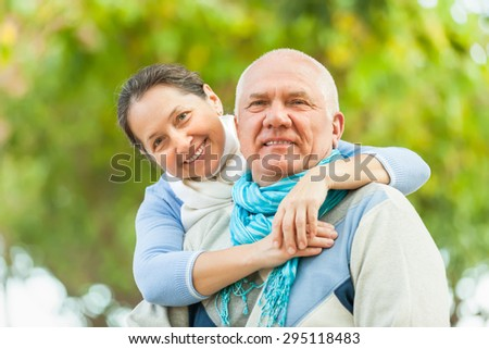Happy mature couple in sweaters walking in autumn park - stock photo