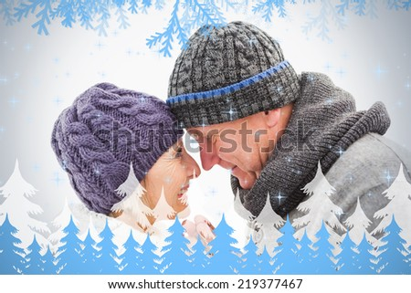 Happy mature couple in winter clothes embracing against frost and fir trees - stock photo
