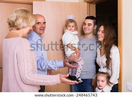 Happy mature couple meeting kids and grand children at doorstep  - stock photo