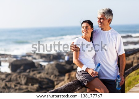happy mature couple relaxing after exercise at the beach - stock photo