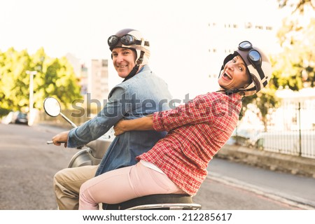 Happy mature couple riding a scooter in the city on a sunny day - stock photo