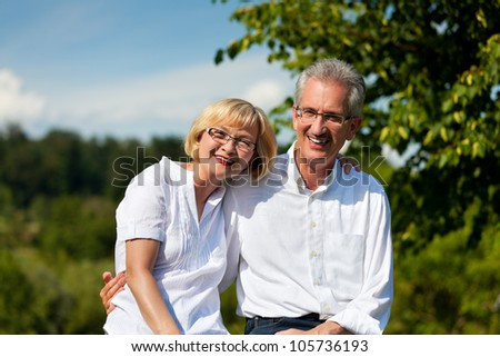 Happy mature couple - senior people (man and woman) already retired - having a walk in summer in nature - stock photo