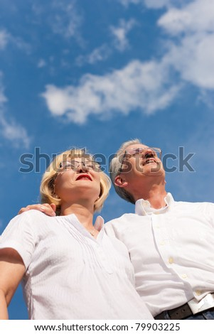 Happy mature couple - senior people, man and woman, already retired - looking to the blue sky in summer feeling free - stock photo