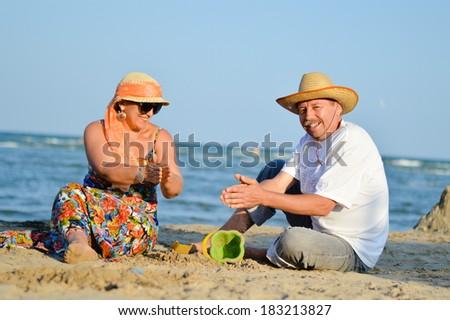 Happy mature couple sitting at seashore on sandy beach - stock photo