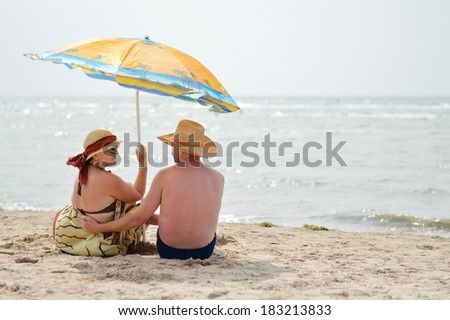 Happy mature couple sitting at seashore on sandy beach back to back - stock photo