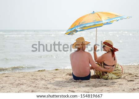 Happy mature couple sitting at seashore on sandy beach back to back on the summer outdoors background - stock photo
